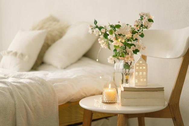 Détails de la nature morte à l'intérieur de la maison du salon. livre, bougie et vase avec fleurs printanières de pomme. lire et se reposer