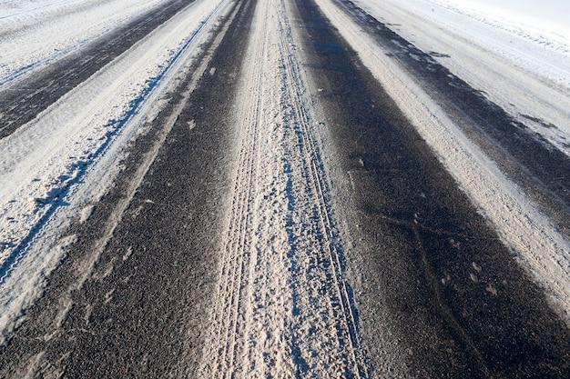 Détails d'une route couverte de neige avec des ornières fondant des voitures