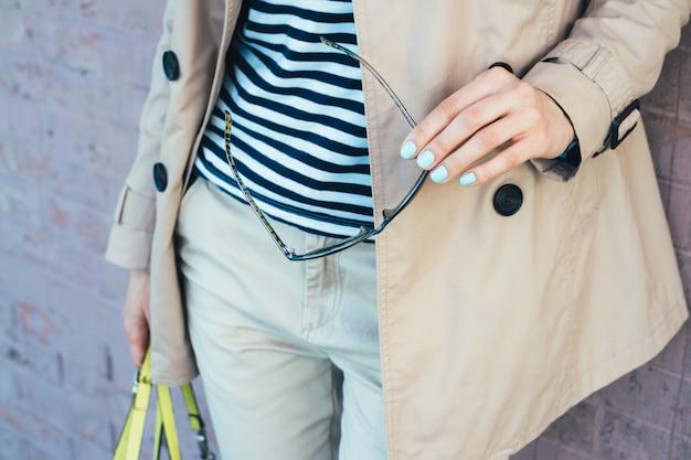Détails de vêtements: femme en manteau beige tenant des lunettes de soleil et un sac à main