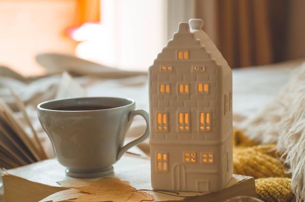 Détails de la vie encore à l'intérieur de la maison du salon. chandails et tasse de thé avec une bougie et un décor d'automne sur les livres. lisez, reposez-vous. concept d'automne ou d'hiver confortable.