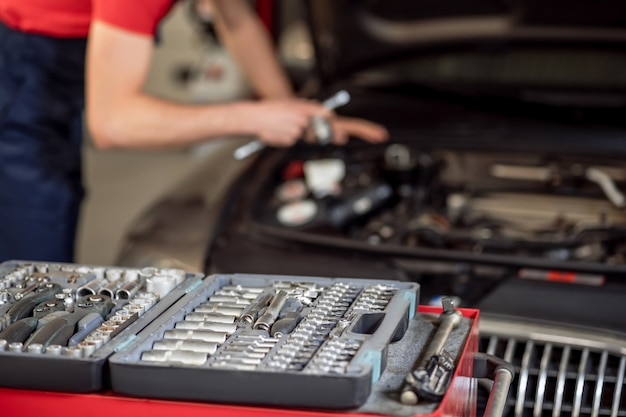 Détails, voiture. boîtier ouvert avec des pièces métalliques et derrière le mécanicien automobile travaillant près du capot de la voiture
