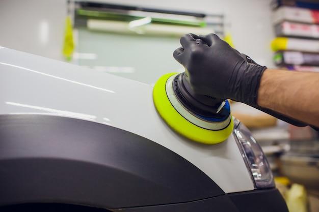 Détails de voiture - mains avec polisseuse orbitale dans un atelier de réparation automobile. mise au point sélective.