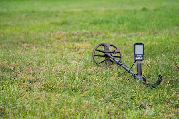 Détecteur de métaux posé à l'extérieur sur l'herbe.
