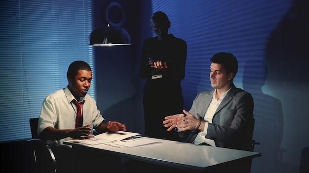 Détective africain interrogeant l'homme caucasien suspect dans la salle d'interrogatoire.