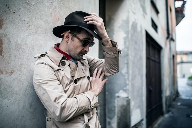 Détective espion homme appuyé contre un vieux mur dans une rangée de dérapage