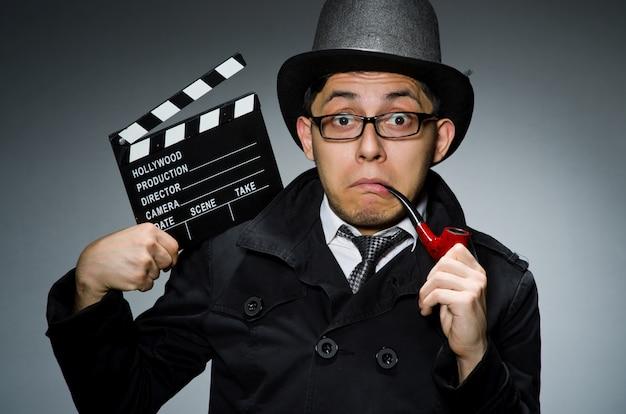 Detective en manteau noir avec clap contre gris