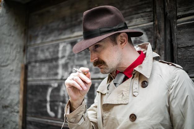 Détective vintage fumant une cigarette dans un bidonville