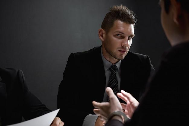 Détectives en salle d'interrogatoire avec suspect ou criminel