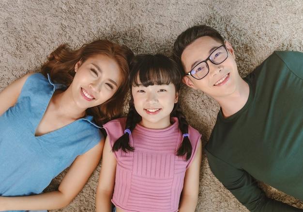 Détendez-vous la famille asiatique pose avec bonheur et sourire sur le tapis dans le salon à la maison. vue de dessus