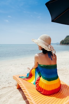 Détendez-vous femme sur une chaise longue sur le ciel de la plage et des nuages.