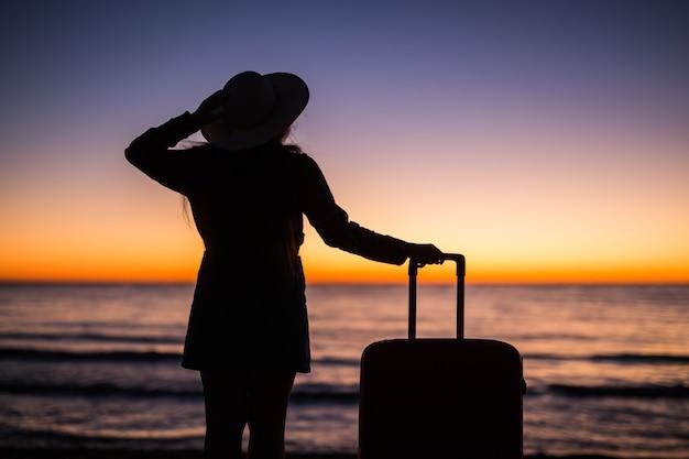 Détendez-vous femme avec valise sur une plage au coucher du soleil silhouette vacances voyage concept jeune femme