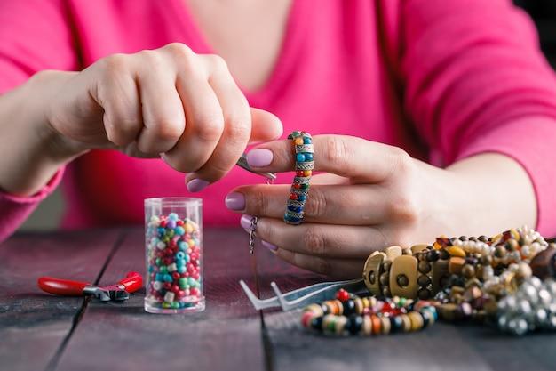 Détendez-vous passe-temps. femme fait des perles artisanales