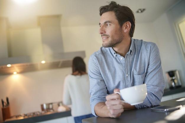 Détendu bel homme dans une cuisine moderne avec femme