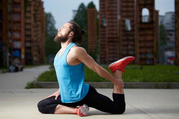 Détendu bel homme faisant des exercices de yoga