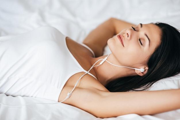Détendu et heureux. jolie jeune femme écoutant de la musique en position allongée sur le lit à la maison