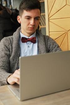 Détendu jeune professionnel surfer sur internet sur son ordinateur portable dans un café
