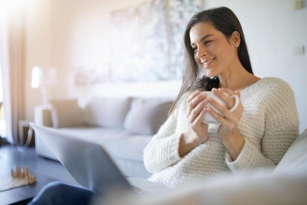 Détendue belle brune avec un ordinateur portable à la maison