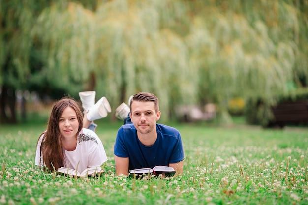 Détendue jeune couple, lire des livres en position couchée sur l'herbe