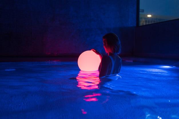 Détendue jeune femme dans la piscine avec néon