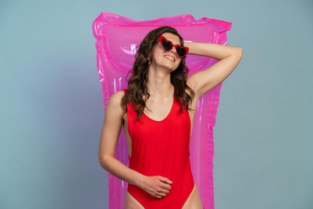 Détendue, jeune fille à lunettes reposant sur un matelas pneumatique
