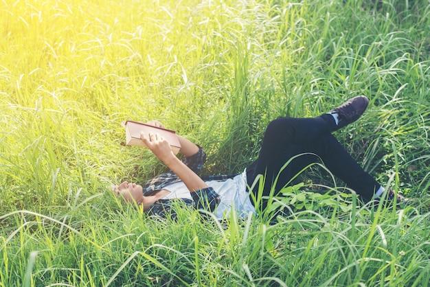Détendue jeune homme lisant extérieur