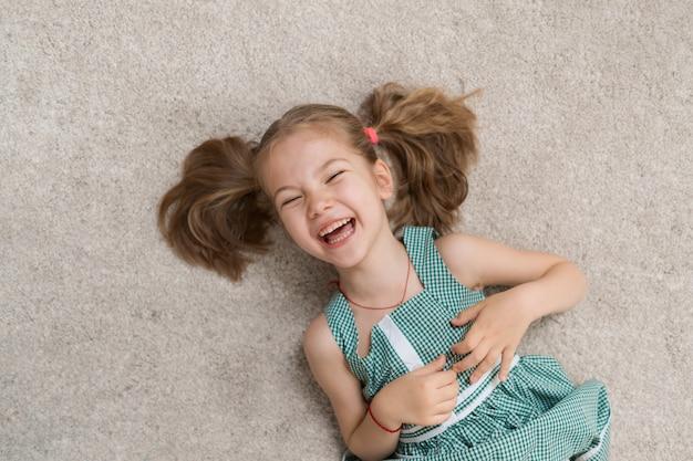 Détendue petite fille allongée sur le sol à l'intérieur et souriant