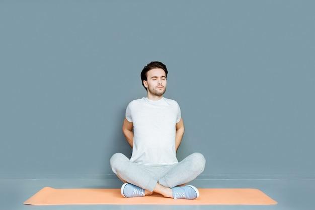 Détente absolue. bel homme agréable et agréable assis sur un tapis de yoga et fermant les yeux tout en pratiquant le yoga