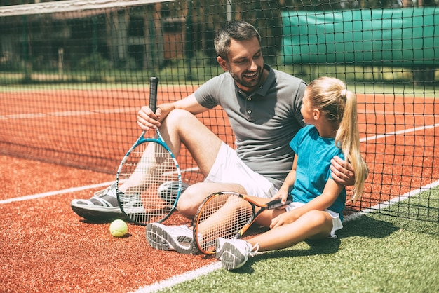 Détente après un bon match. joyeux père et fille se penchant sur le filet de tennis et se regardant avec des sourires alors qu'ils étaient tous les deux assis sur un court de tennis