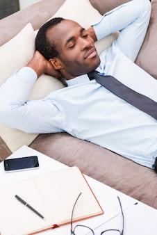 Détente après le travail. vue de dessus du beau jeune homme africain en chemise et cravate