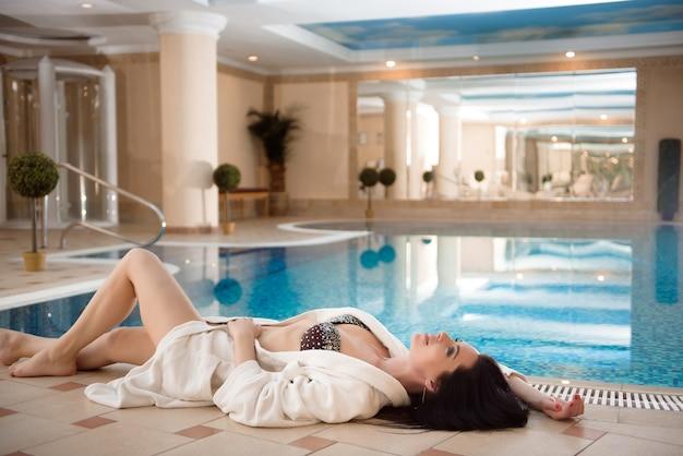 Détente au spa. belle fille caucasienne sexy en bikini près de la piscine dans le salon spa de jour de villégiature.