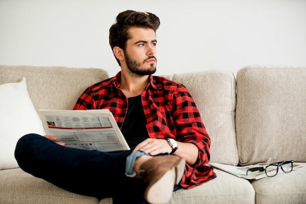 Détente sur le canapé. gentil jeune homme tenant un journal et regardant loin alors qu'il était assis sur un canapé