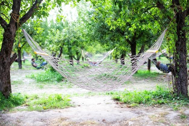 Détente dans un hamac dans le jardin. jardin d'été avec hamac suspendu pour se détendre. hamac de voyage agrandi pour se détendre dans les arbres. concept de loisirs de plein air. hamac en maille de corde blanche suspendue à des cordes