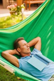 Détente dans un hamac. heureux homme mûr dormant en position couchée dans un hamac avec un livre posé sur son torse