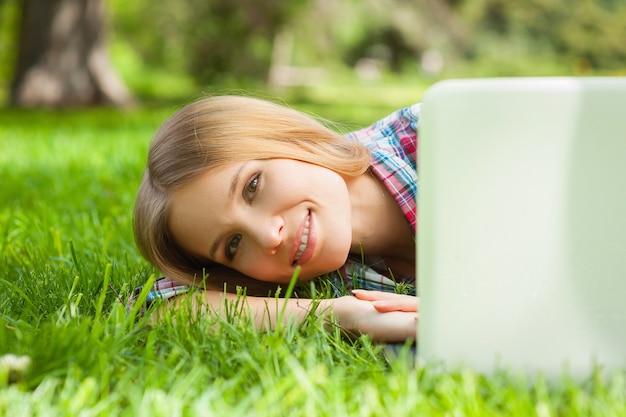 Détente dans le parc. belle jeune étudiante à la recherche d'un écran d'ordinateur portable et souriant en position couchée sur l'herbe dans le parc