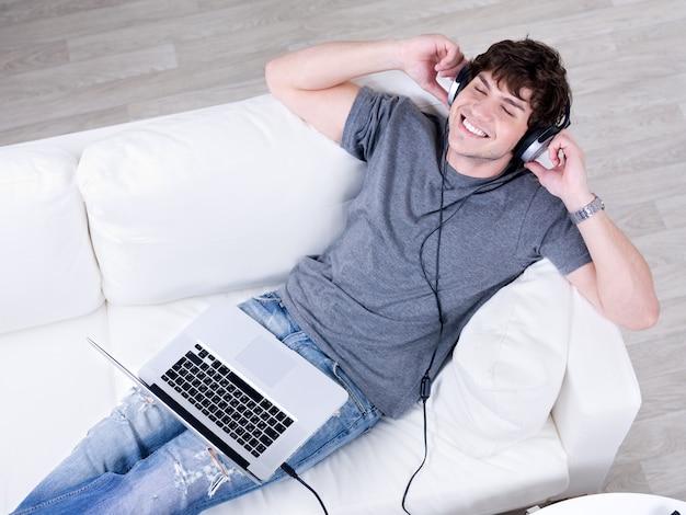 Détente du jeune homme heureux allongé sur le canapé avec ordinateur portable et écouter de la musique au casque