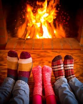 Détente en famille à la maison. pieds dans des chaussettes de noël près de la cheminée. concept de vacances d'hiver