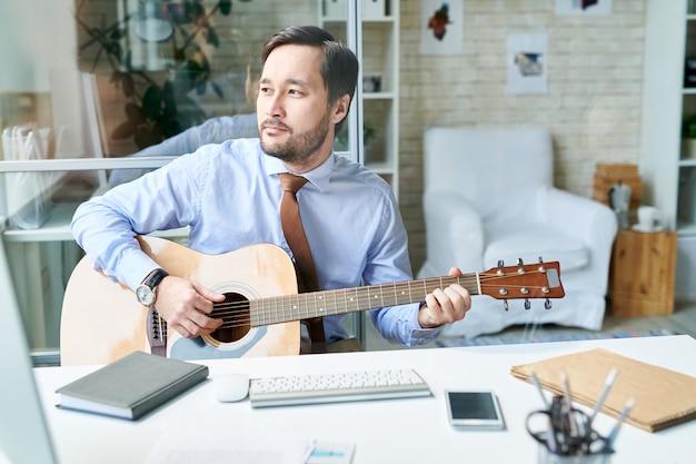 Détente homme au bureau, jouer de la guitare