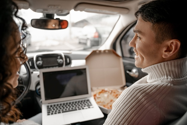 Détente de jeune couple européen dans la cabine de la voiture. homme et femme se regardant et souriant. pizza et ordinateur portable sur fond de personnes. concept de profiter du temps ensemble