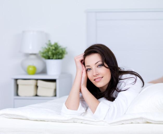 Détente sur un lit de belle jeune femme brune