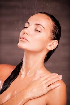 Détente sous la douche. belle jeune femme torse nu debout dans la douche et gardant les yeux fermés