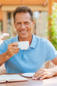 Détente avec une tasse de café frais. homme mûr gai buvant du café et souriant tout en étant assis à la table à l'extérieur avec la maison en arrière-plan