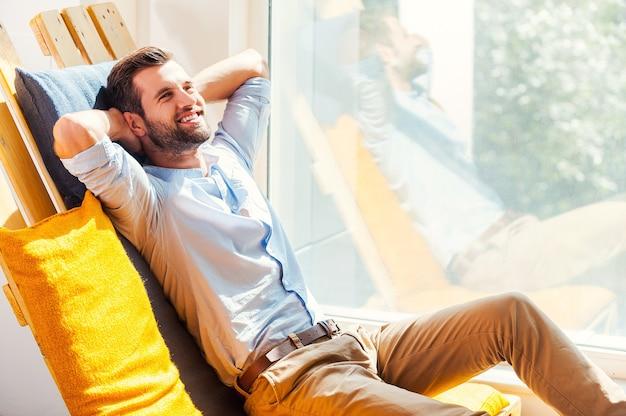 Détente totale. gai jeune homme tenant la tête dans les mains et souriant alors qu'il était assis dans l'aire de repos du bureau