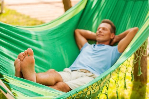 Détente totale. heureux homme mûr allongé dans un hamac et lisant un magazine