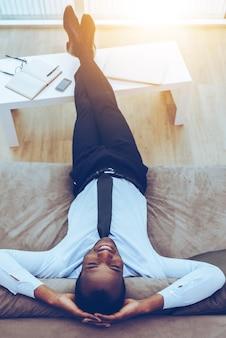Détente totale. vue de dessus de l'heureux jeune homme africain en tenue de soirée allongé sur le canapé avec ses jambes sur un bureau et les mains derrière la tête