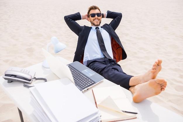 Détente totale. vue de dessus d'un jeune homme détendu en tenue de soirée et lunettes de soleil tenant les mains derrière la tête et tenant ses pieds sur la table debout sur le sable