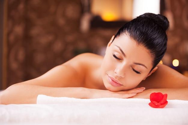 Détente totale. vue de face d'une belle jeune femme torse nu allongée sur une table de massage et gardant les yeux fermés