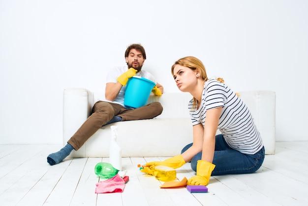 Détergent domestique homme et femme, nettoyage ensemble intérieur.