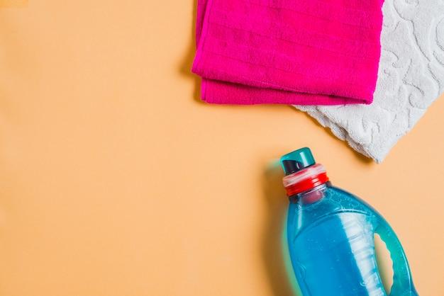 Détergent à lessive avec deux serviettes sur fond coloré