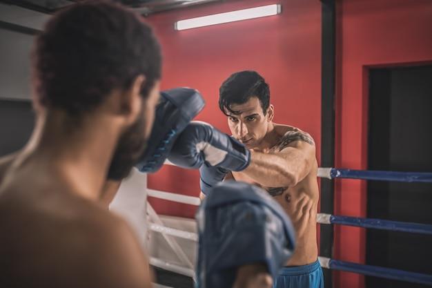 Détermination. jeunes hommes combattant sur un ring de boxe et semblant déterminés