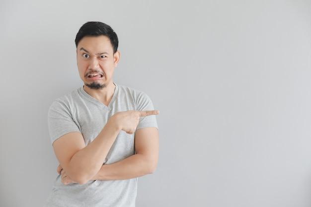 Déteste le visage de l'homme en t-shirt gris avec la main pointée sur un espace vide.